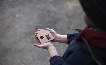 person holding a small cardboard house