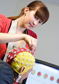 researcher placing EEG cap on patient
