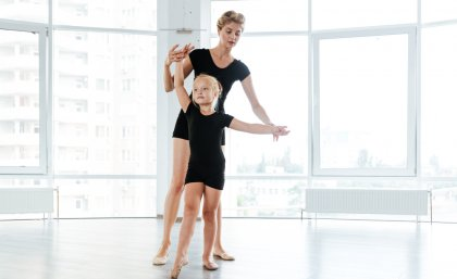 child receiving dancing lessons from an instructor