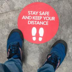 person's feet standing on a social distancing reminder sticker