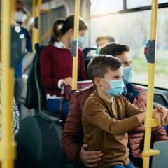 man and son riding on bus with masks