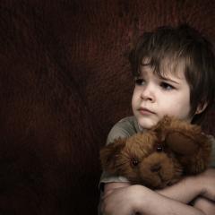 child holding toy bear looking sad