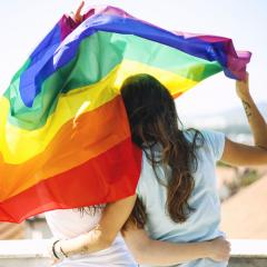 women hugging holding a rainbow flag