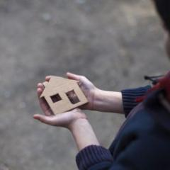 Person holding a small cardboard house  in their hands