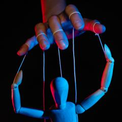 hand controlling a mannequin like a puppet