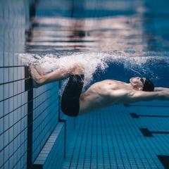Pro male swimming turning under water