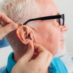 elderly man having hearing aid fitted