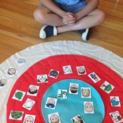 child sat on mat placing items in circle