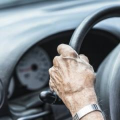 older hands on the steering wheel